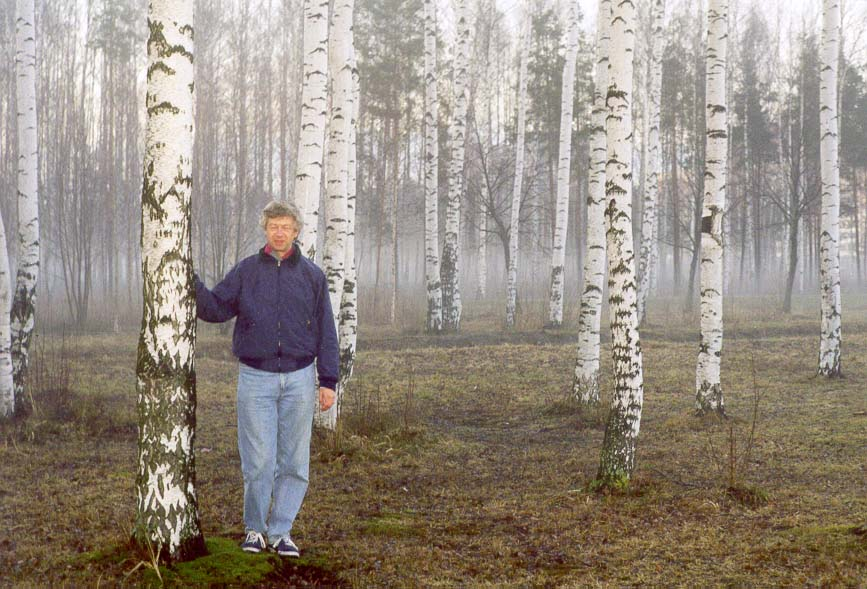 A. V. Sergeev among birches in Sosnovka Park with evening fog. St.Petersburg, Russia