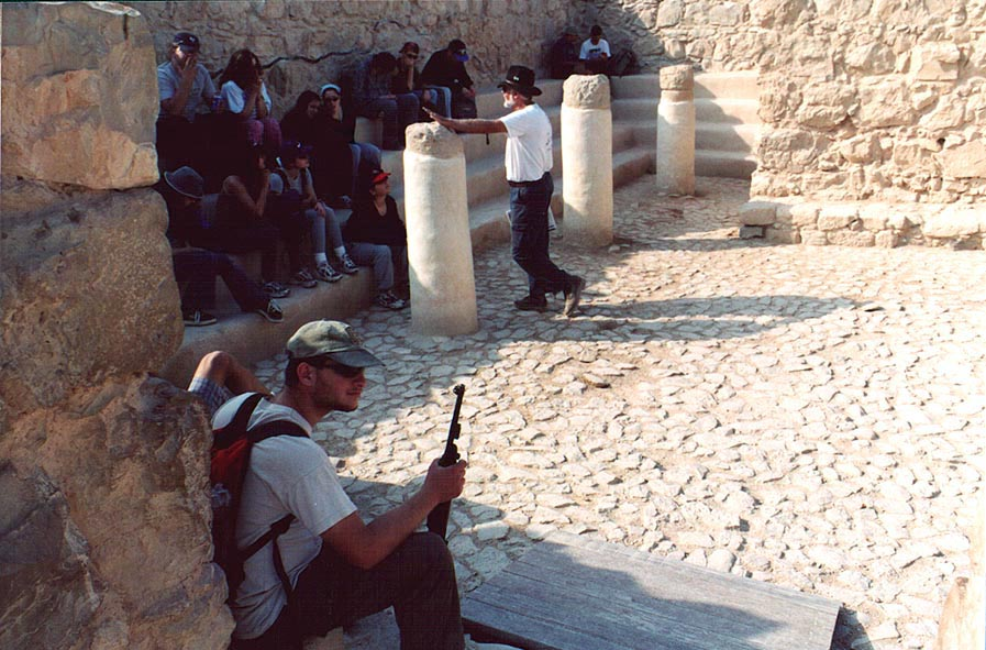 A person with a machine gun with a group of...synagogue at Masada. The Middle East