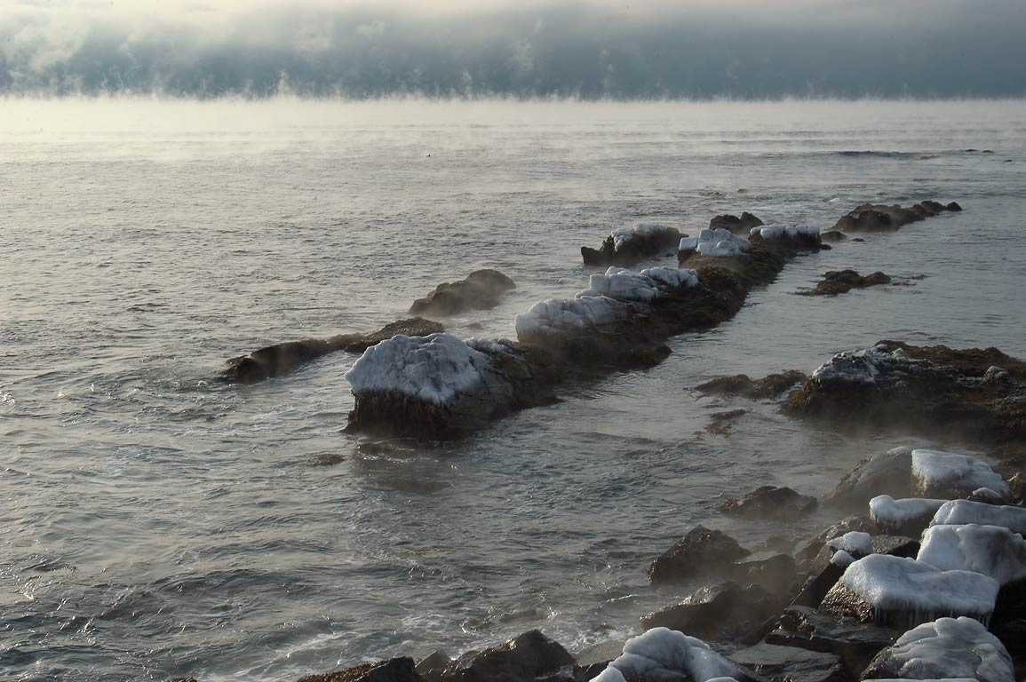 Sea smoke in Sheep Point Cove, view from Cliff Walk trail. Newport, Rhode Island