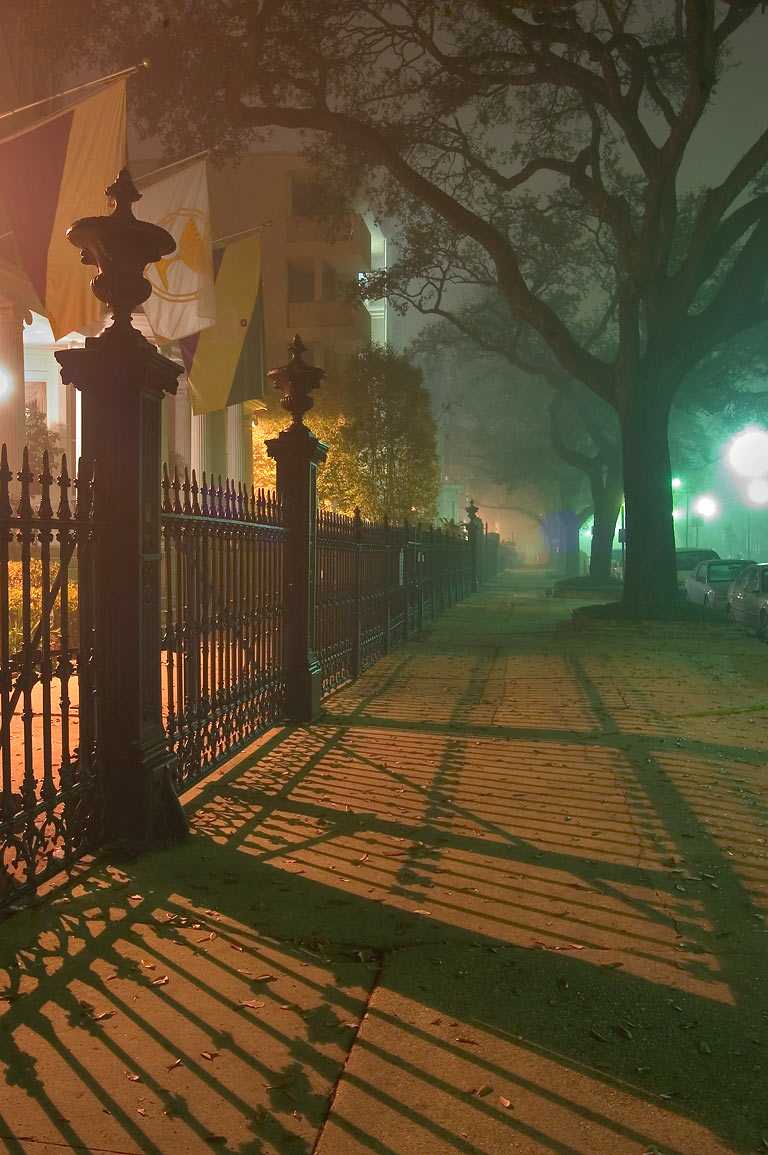 A fence and its shadow on a sidewalk in fog near...at night. New Orleans, Louisiana