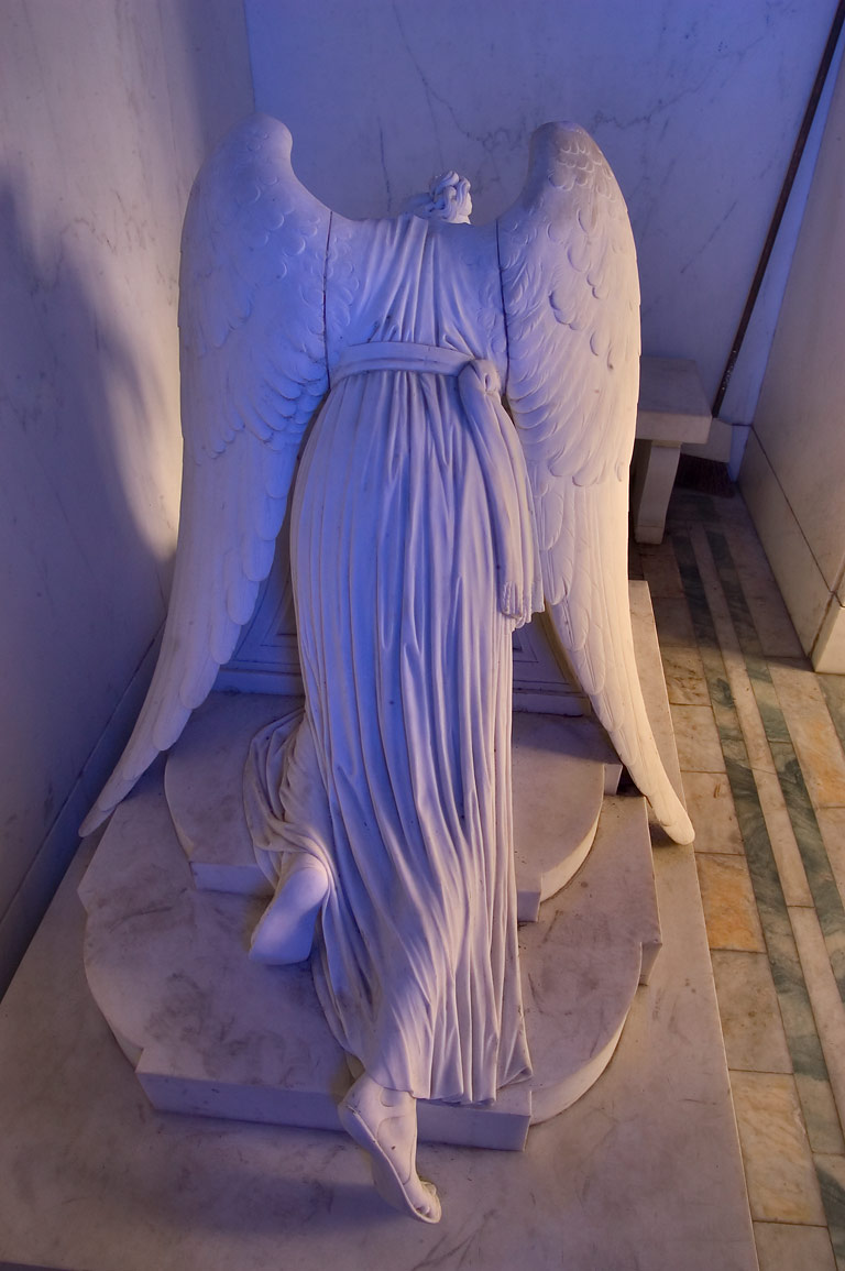 Tail side of a blue weeping angel in a crypt of...Cemetery. New Orleans, Louisiana