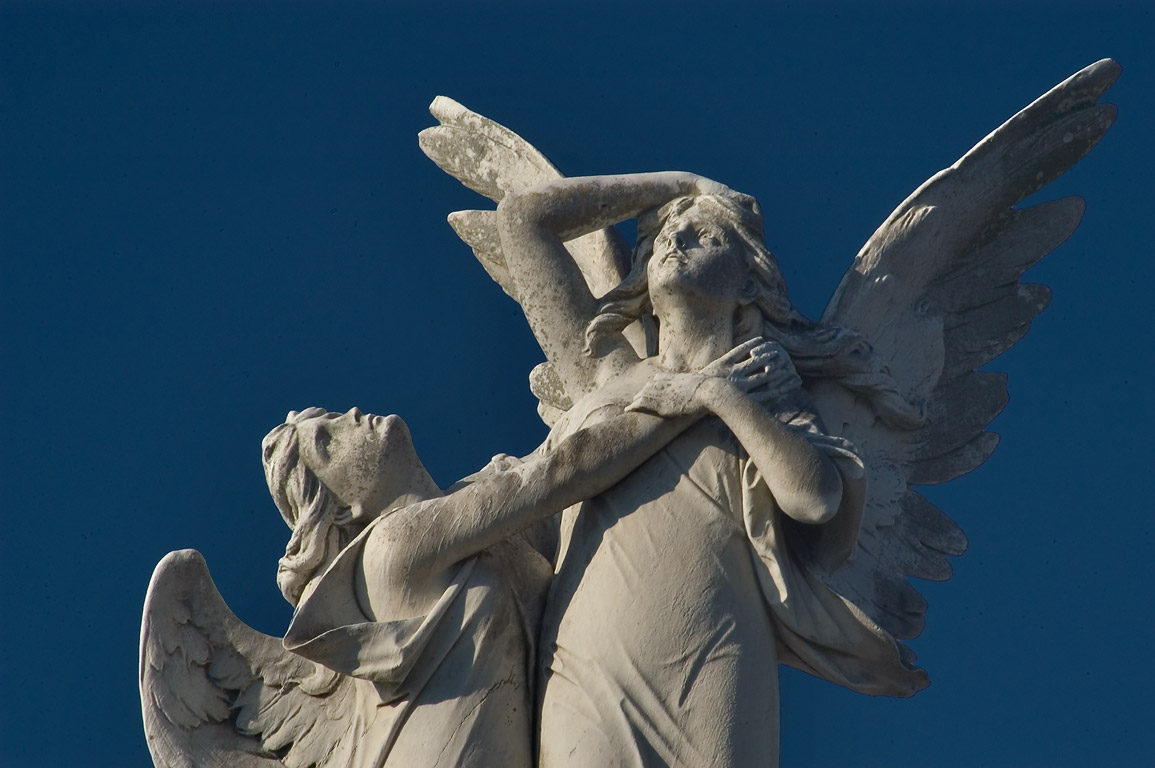 Marble angels clasping each other over a tomb of...Cemetery. New Orleans, Louisiana