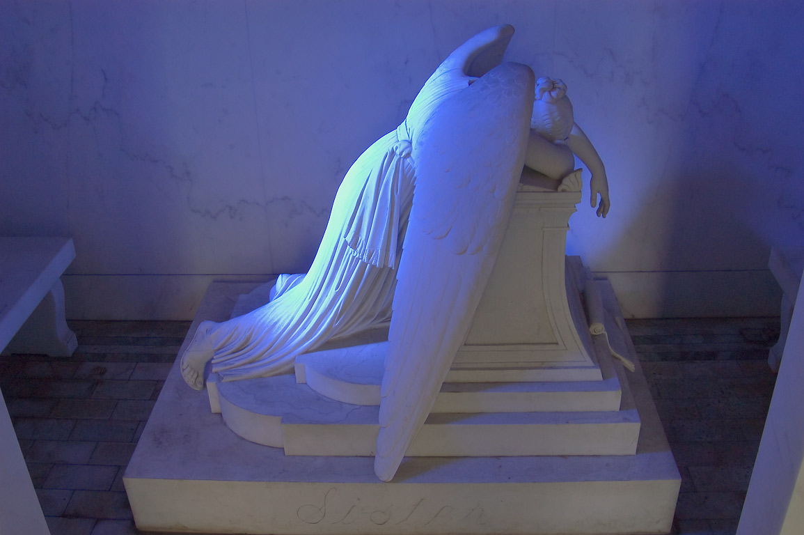 Weeping angel illuminated through blue stained...Cemetery. New Orleans, Louisiana