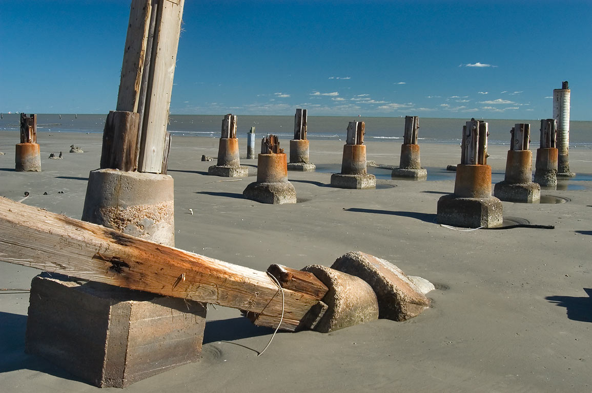 Pilings of Murdoch's Bathhouse, a gift shop and...and Gulf of Mexico. Galveston, Texas