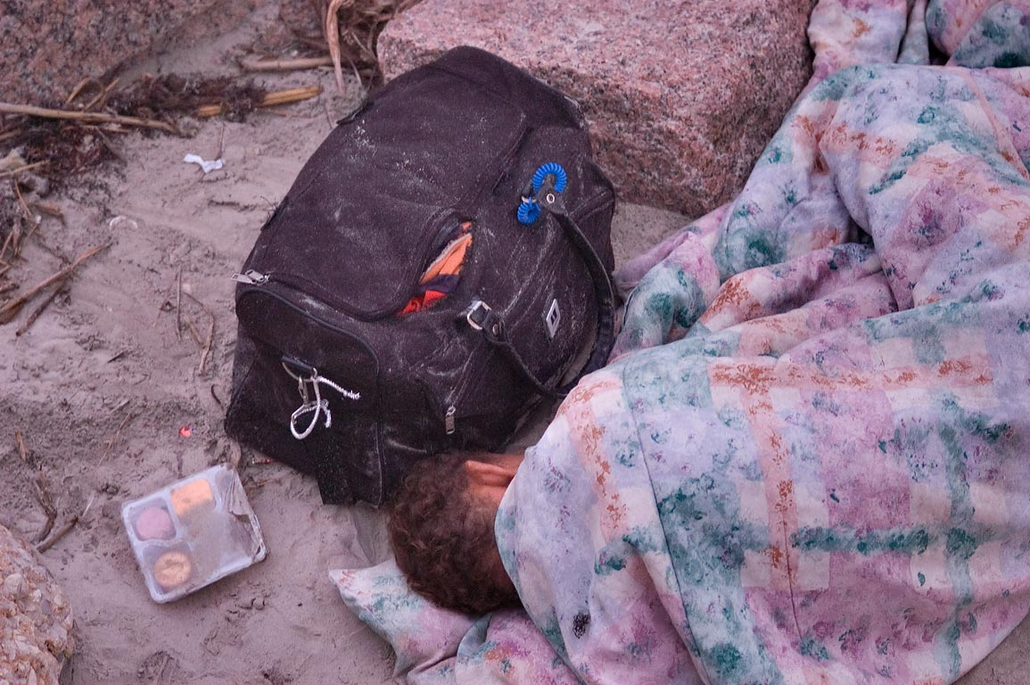 Homeless person sleeping on a beach under seawall near 19th St.. Galveston, Texas