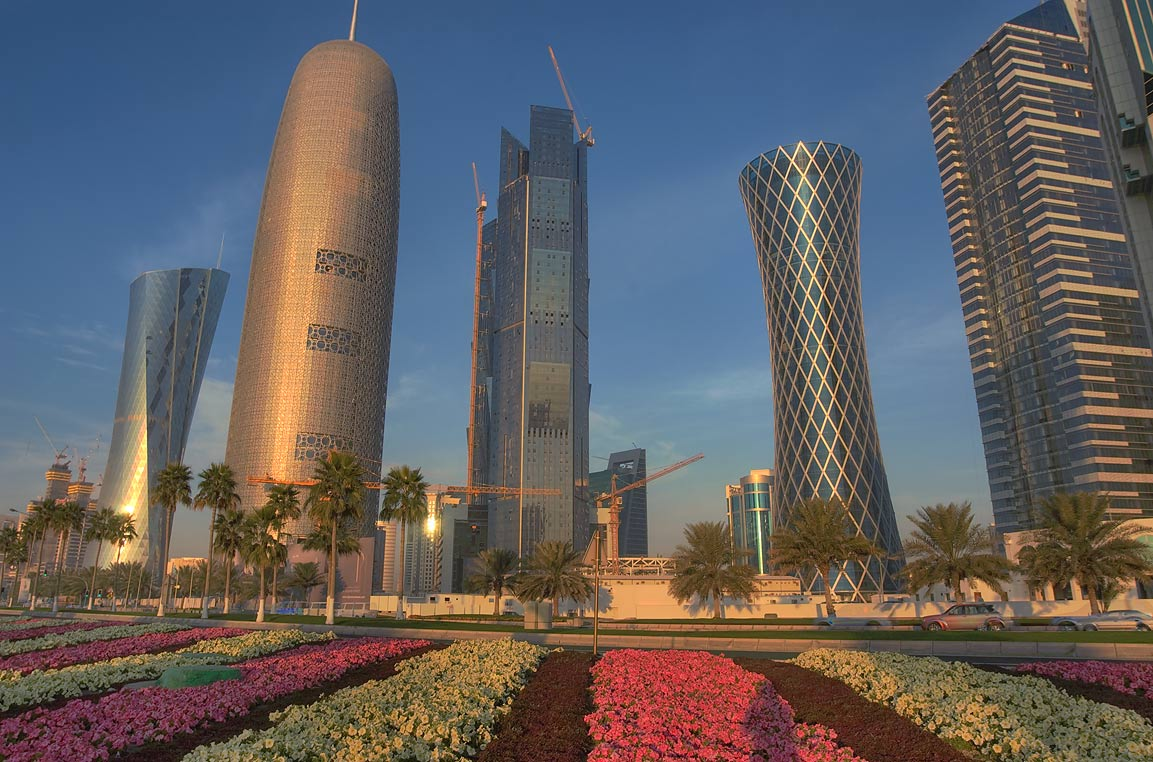 Flower beds opposite to giant tea pot and West...from Corniche at sunrise. Doha, Qatar
