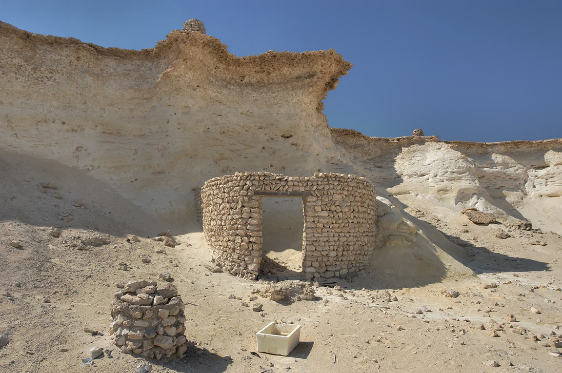 Stone hut nestling under a limestone cliff...area, north from Zekreet. Qatar