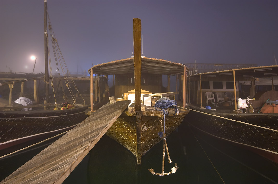 Dhow fishing boat moored in port at morning in fog. Doha, Qatar