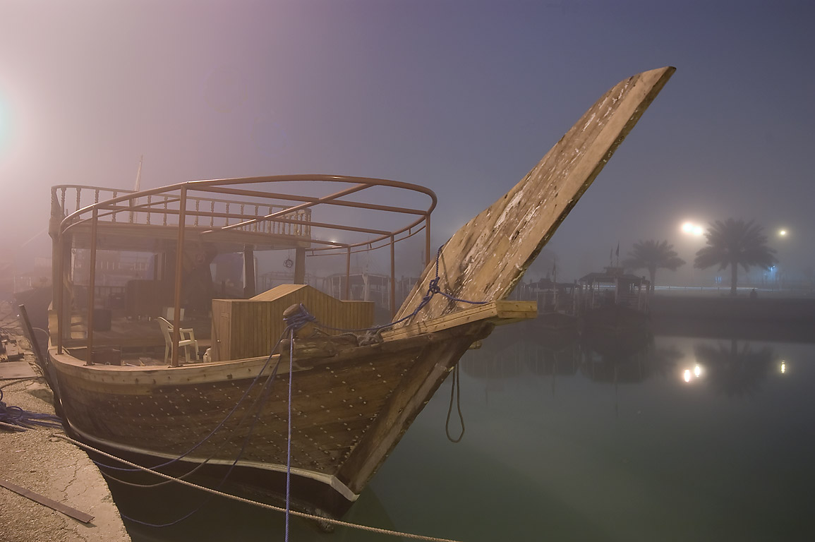 Dhow boat in a port at morning in fog. Doha, Qatar