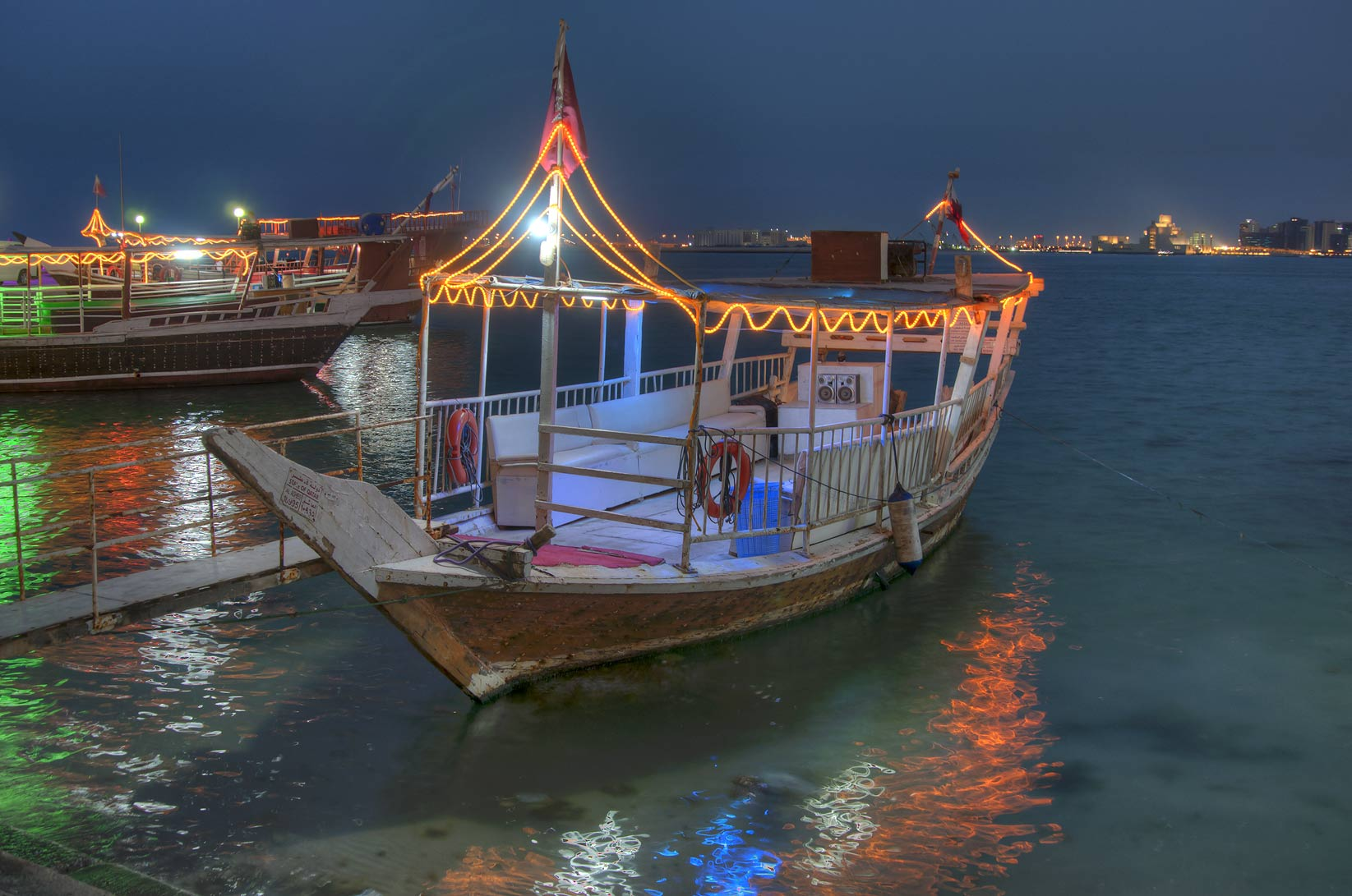Dhow traditional fishing boat docked at Corniche...promenade) at evening. Doha, Qatar