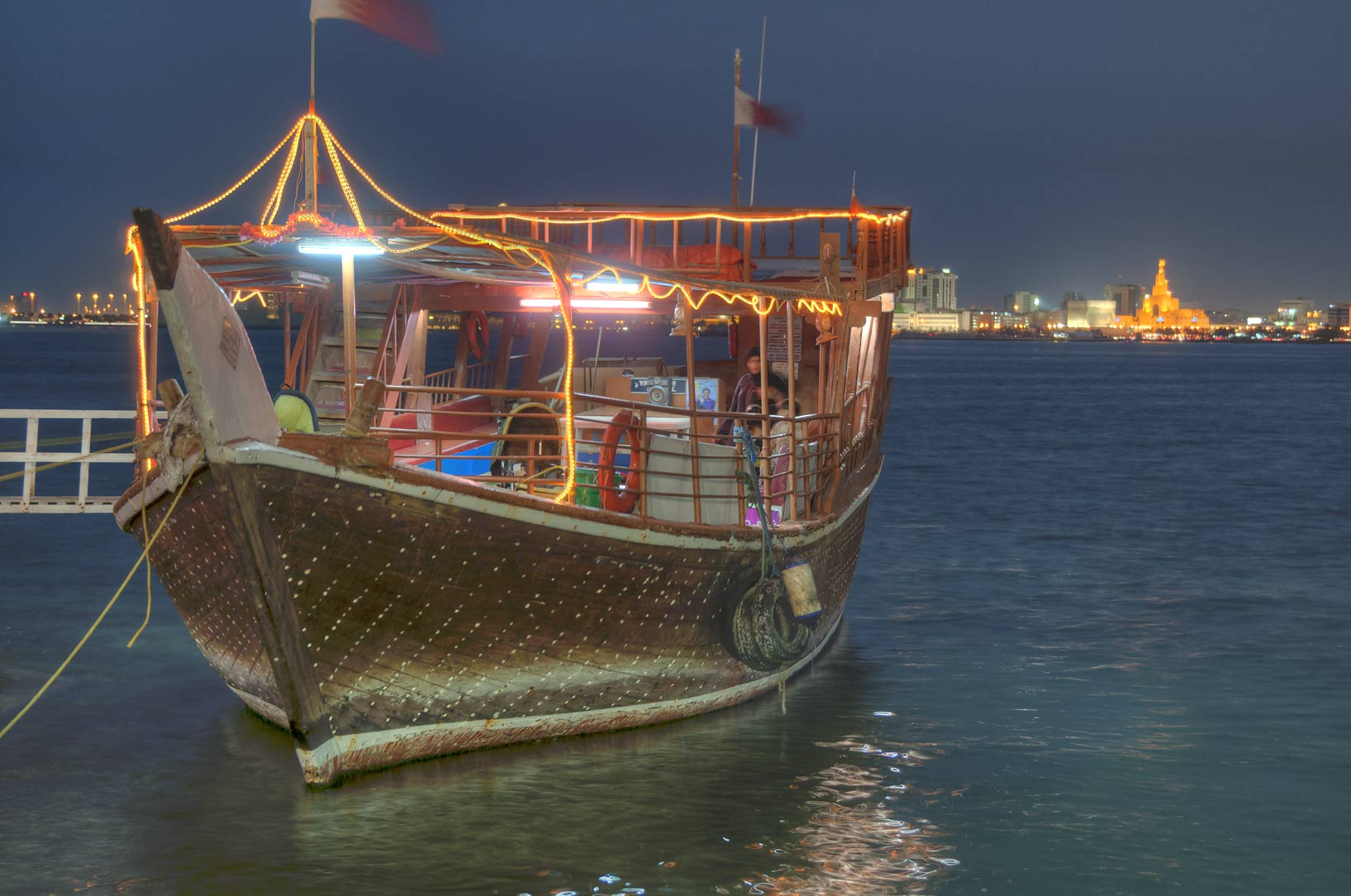 Dhow boat for tourists docked at Corniche at evening. Doha, Qatar