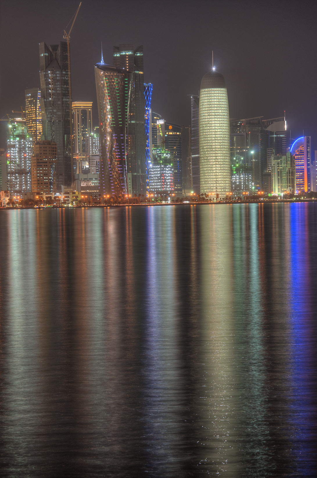 West Bay lights reflected in Persian Gulf from Corniche at evening. Doha, Qatar