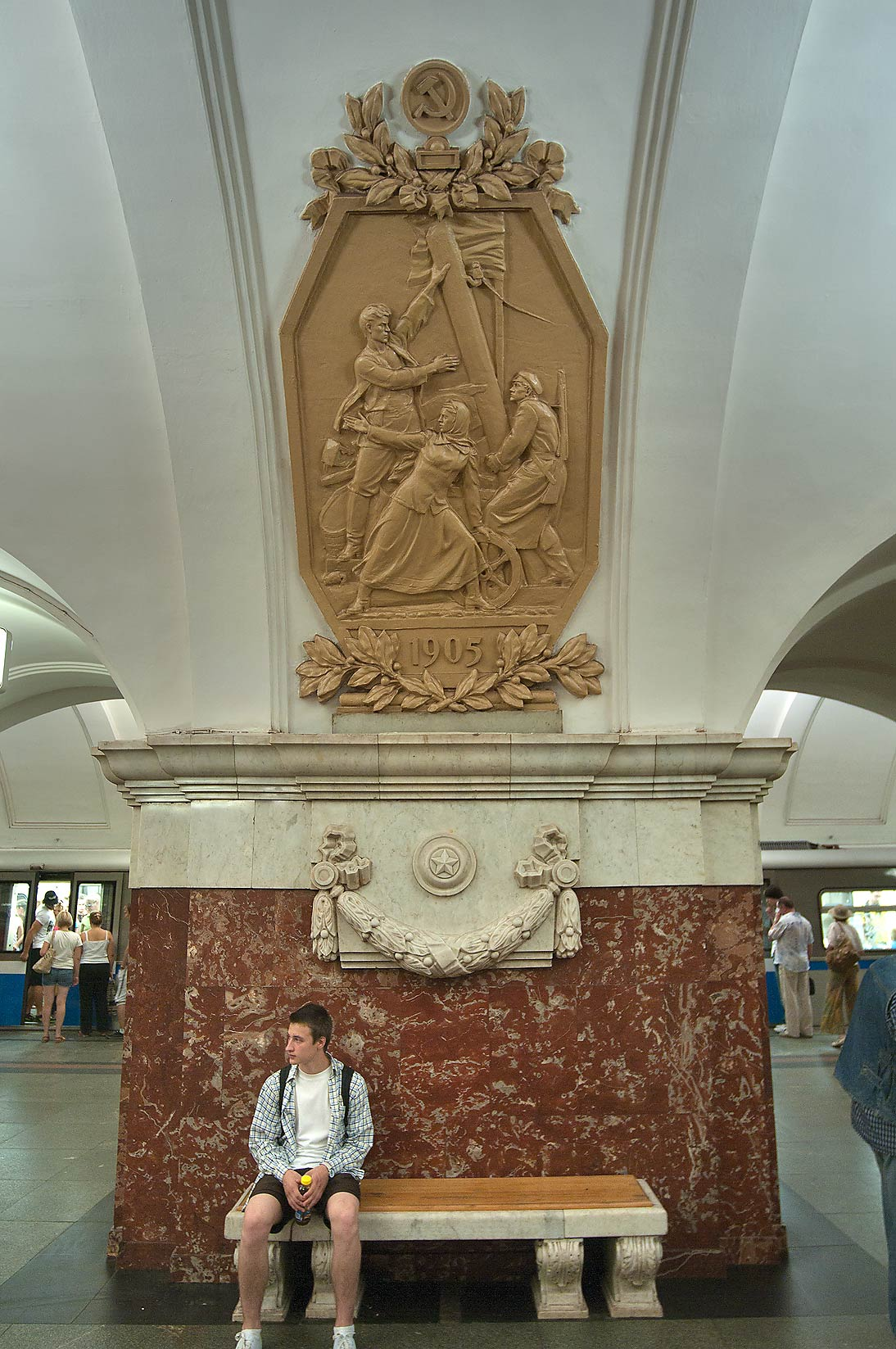 Passenger sitting under illustration of first...Metro (subway) station. Moscow, Russia