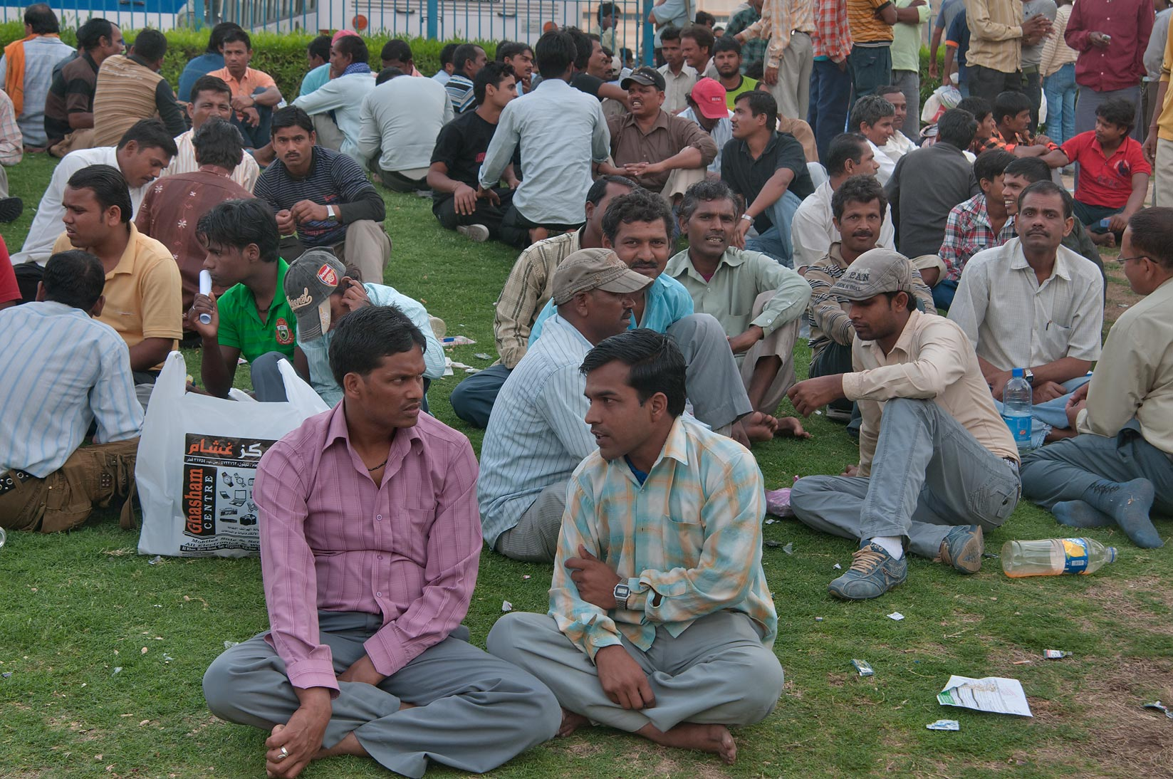 Migrant workers sitting on a lawn at Central Bus Station Al Ghanim on Friday. Doha, Qatar