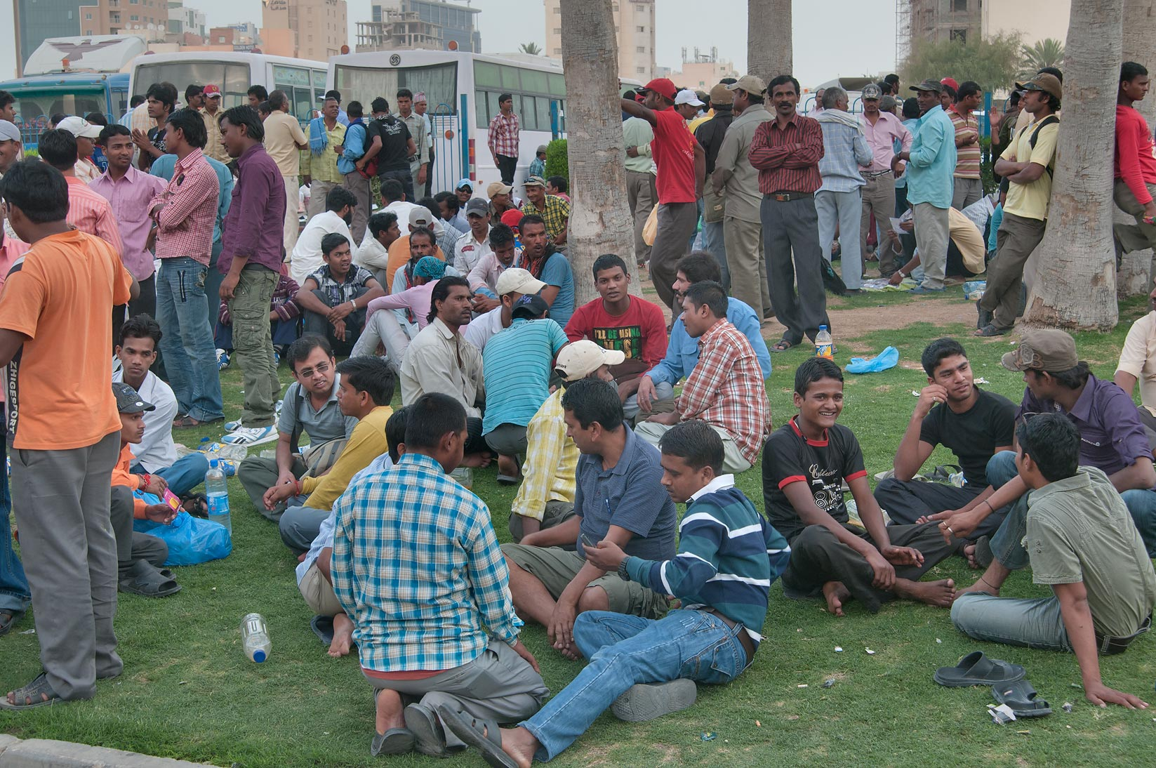 Migrant workers talking on a lawn at Central Bus Station Al Ghanim on Friday. Doha, Qatar