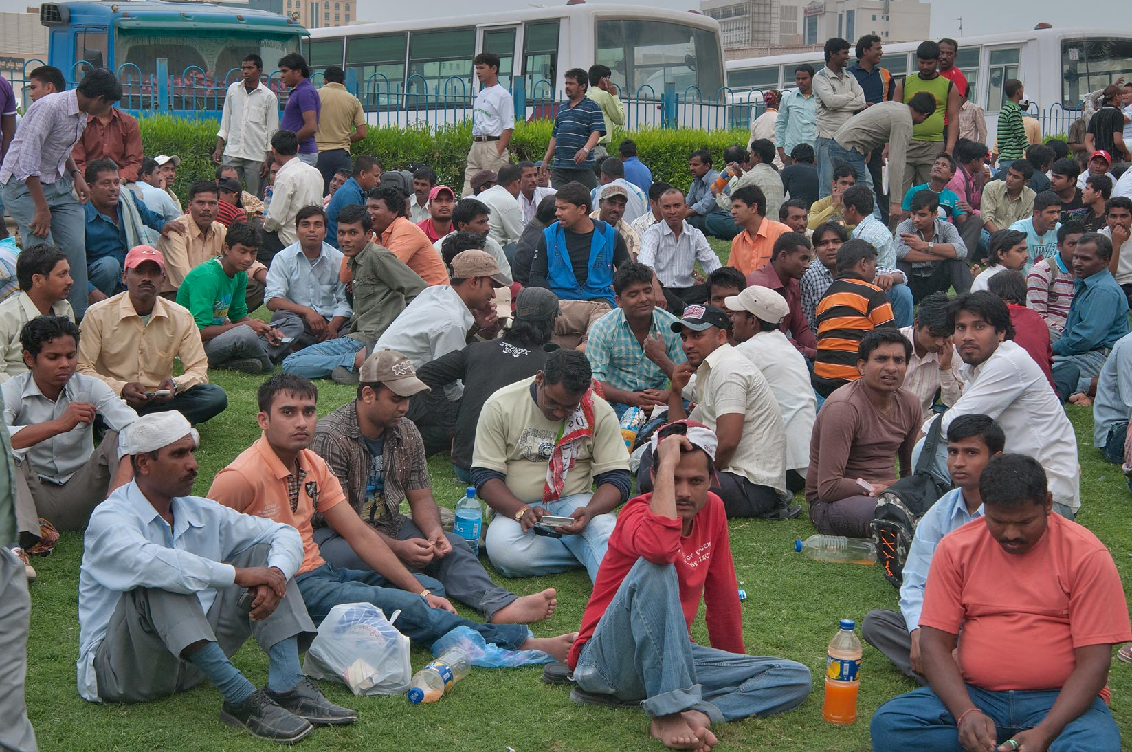 Workers sitting on a lawn on Friday evening at Central Bus Station Al Ghanim. Doha, Qatar