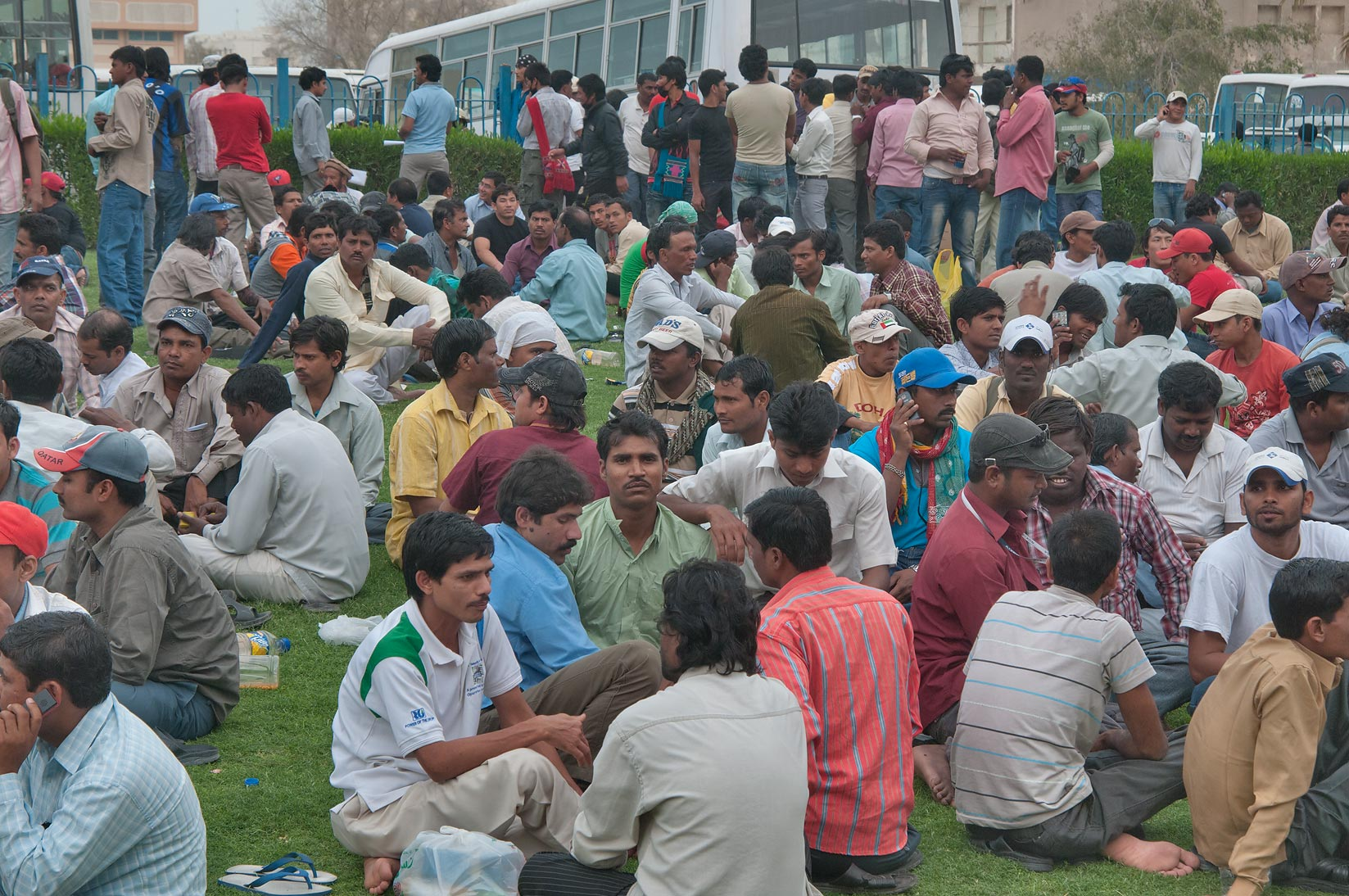 Migrant workers crowding on a lawn on Friday...Bus Station Al Ghanim. Doha, Qatar