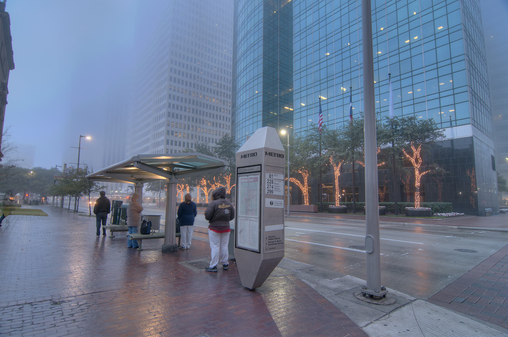 Passengers at bus stop in downtown in fog. Houston, Texas