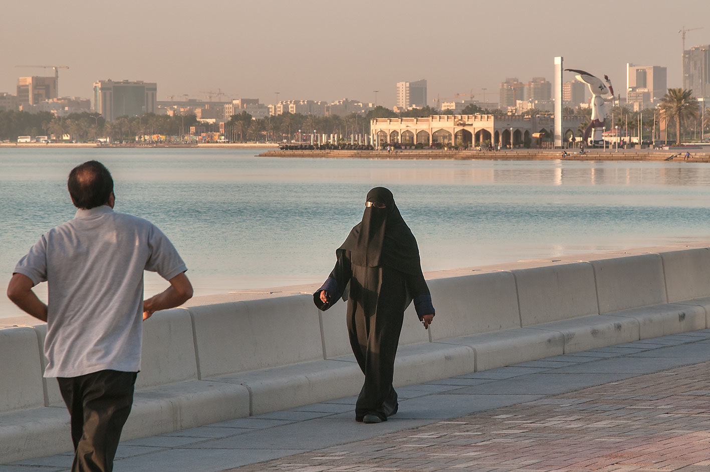 People jogging on Corniche promenade at morning. Doha, Qatar