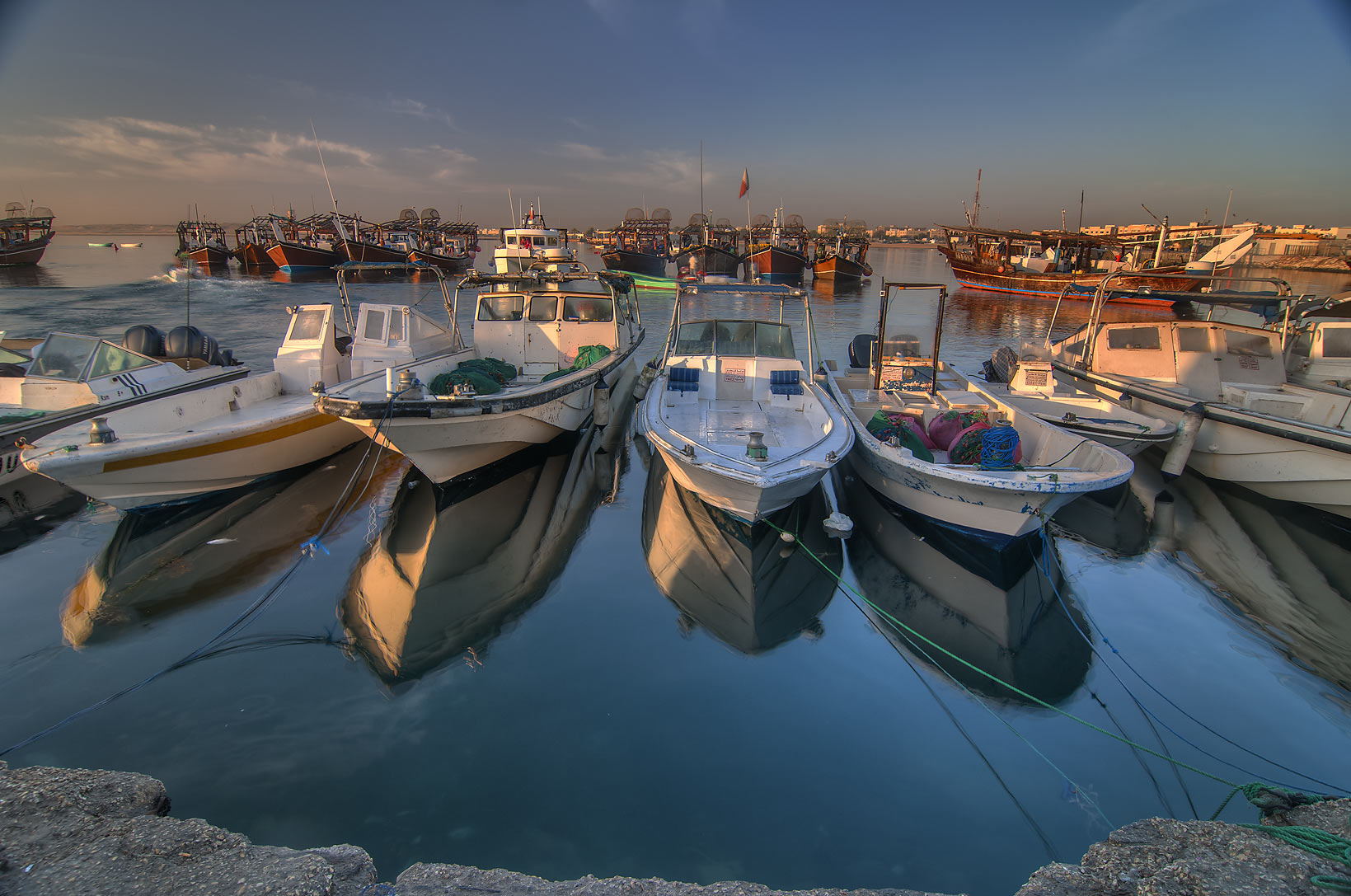 Reflections of fishing boats in harbor in Al Wakra, view from a pier. Qatar
