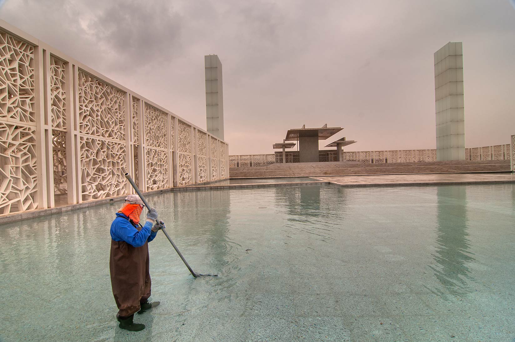 Cleaning a pool of Ceremonial Court in Education City at rain. Doha, Qatar