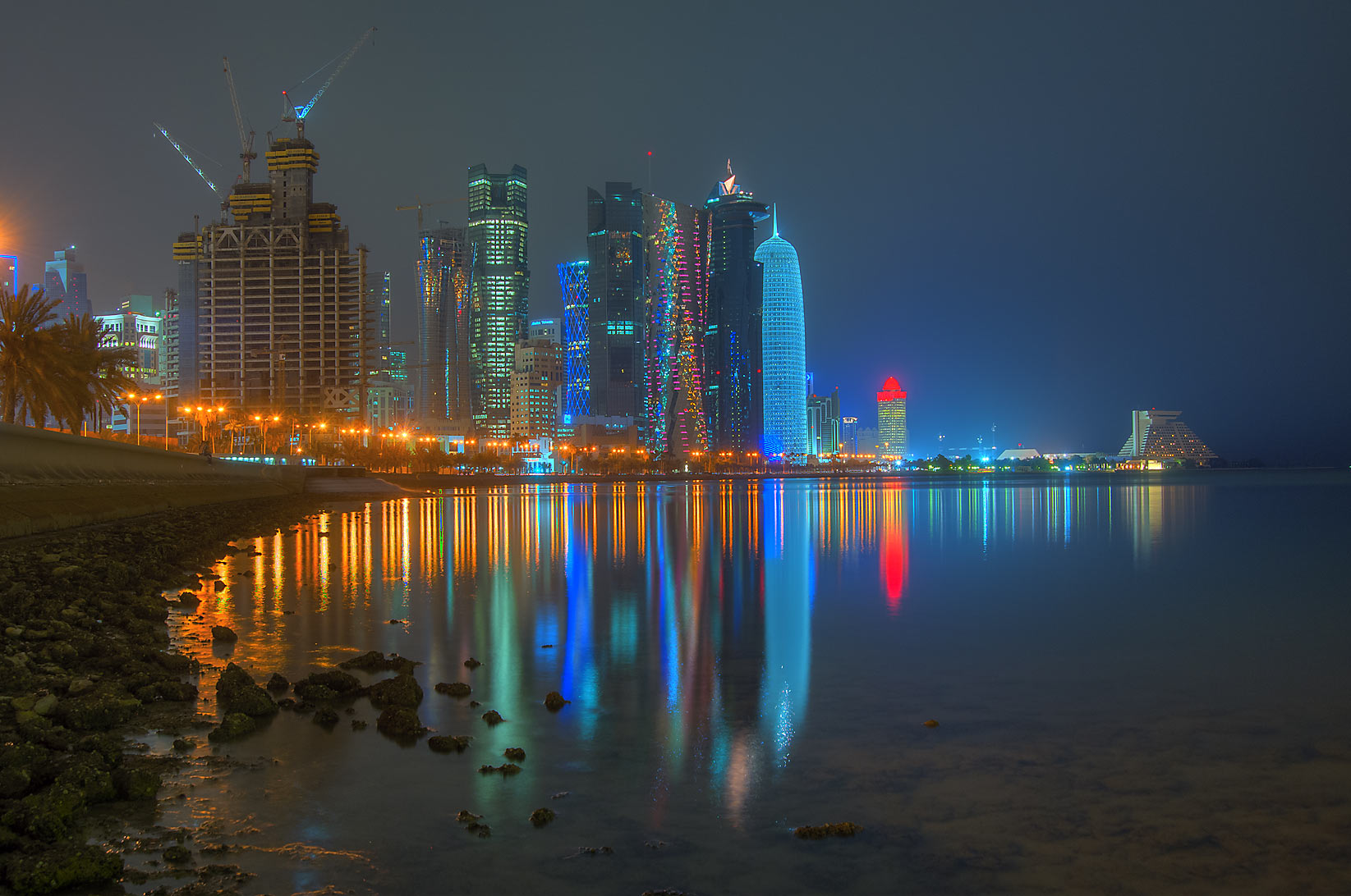 Reflections of West Bay from Corniche promenade at low tide at morning dusk. Doha, Qatar