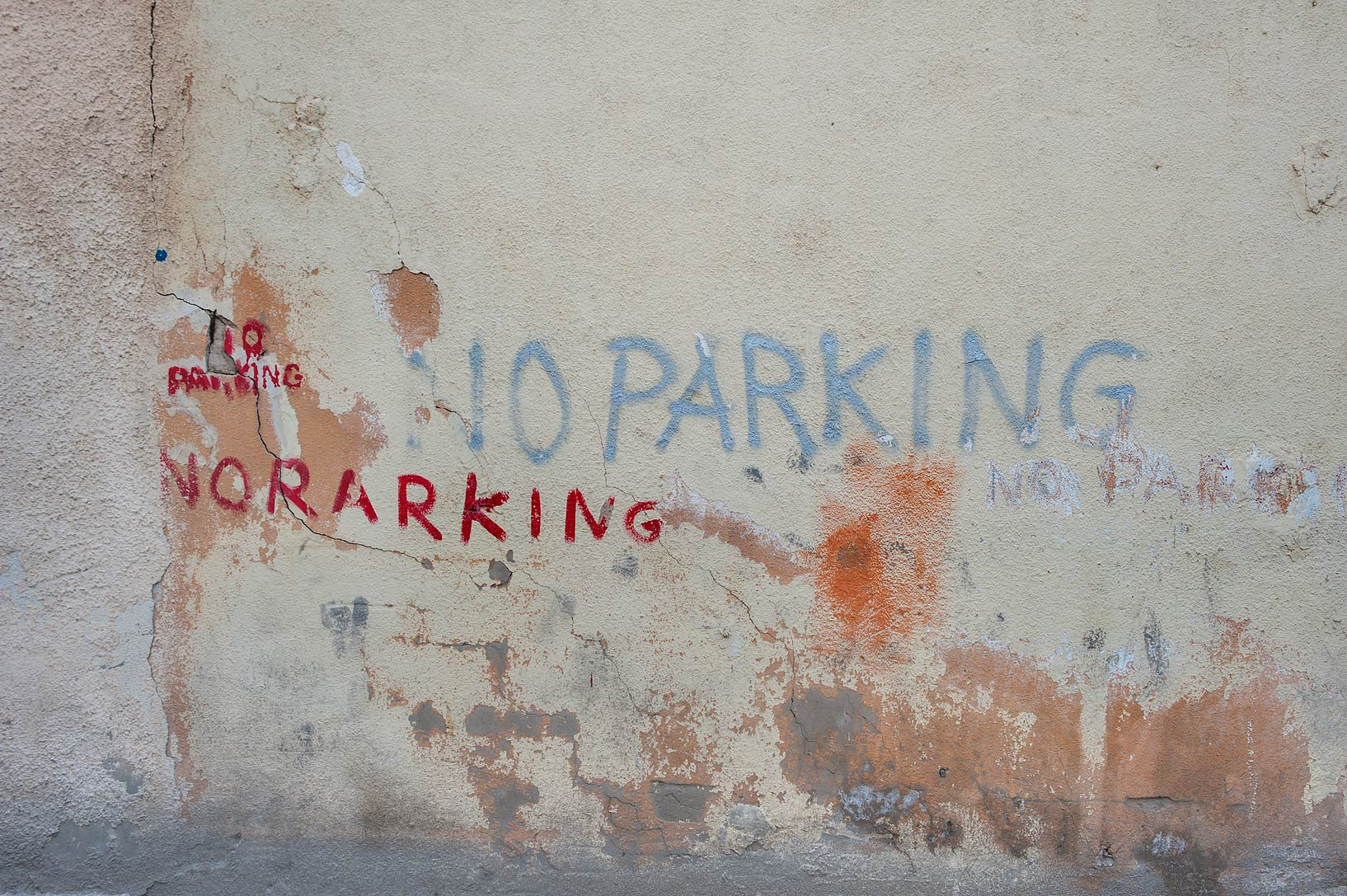 Parking signs written on a wall on Bishr Bin Al Baraa St. in Najma area. Doha, Qatar