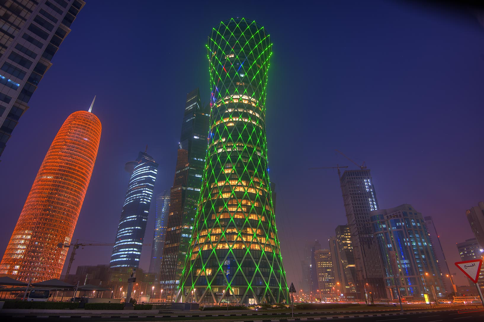Green lights of Tornado Tower in West Bay at morning dusk. Doha, Qatar