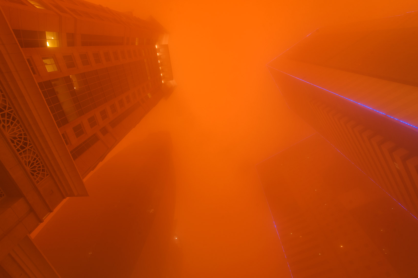 Al Gassar Tower and Ezdan Hotel in West Bay in orange light from a dust storm. Doha, Qatar
