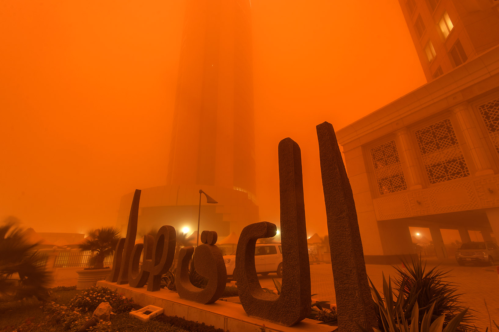 Entrance of Al Gassar Tower in West Bay in orange light from a dust storm. Doha, Qatar