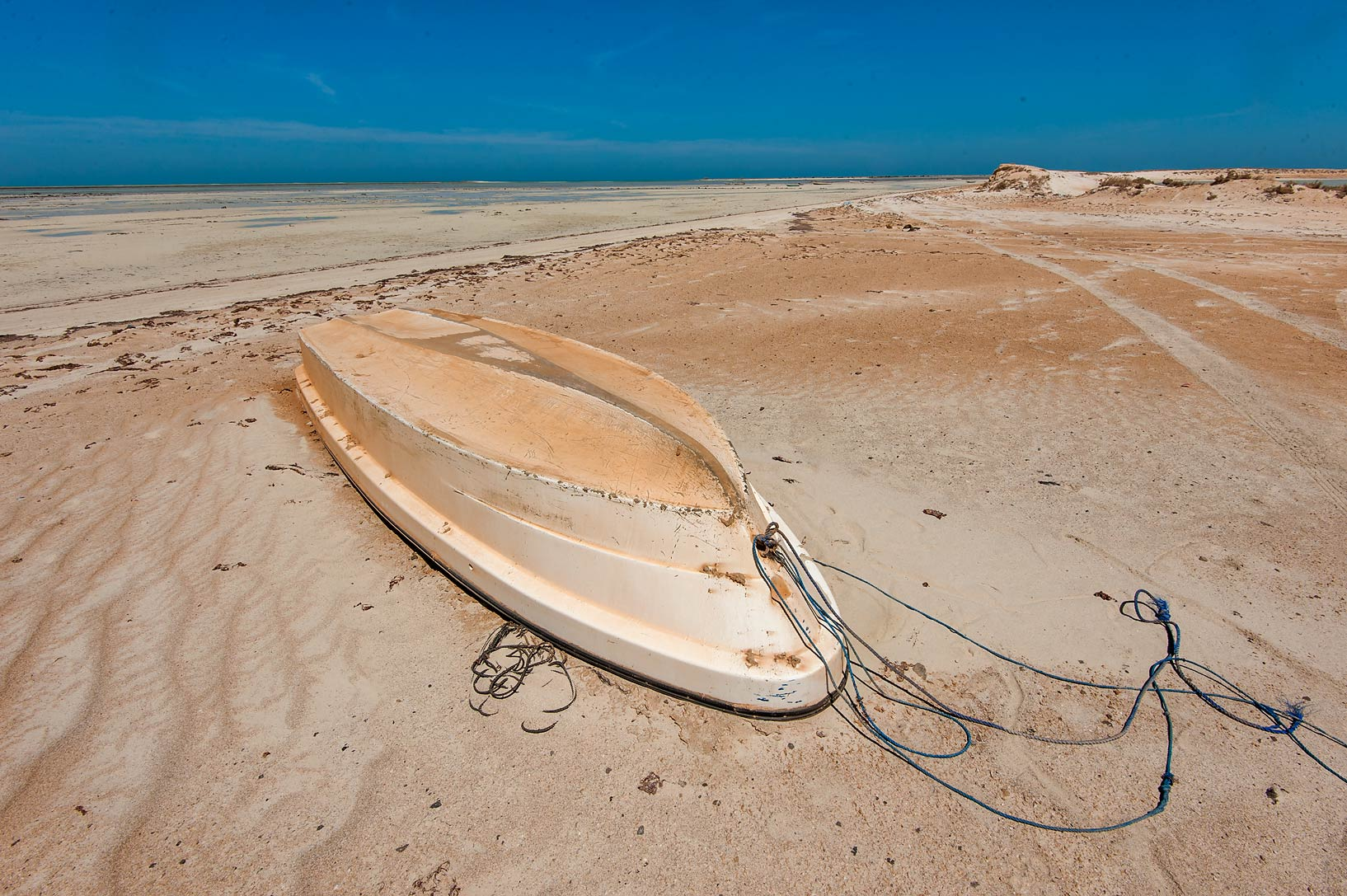 Dusty boat on a beach in Khasooma area. Ruwais, Northern Qatar