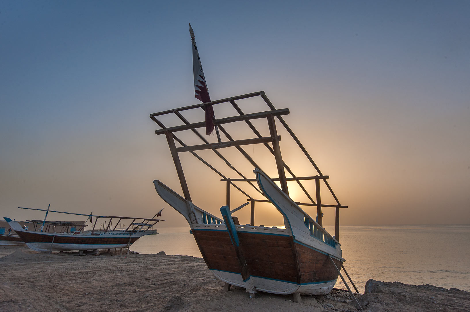 Dhow fishing boat on a beach against sun in Al...Souq Waqif in Al Wakrah). Qatar
