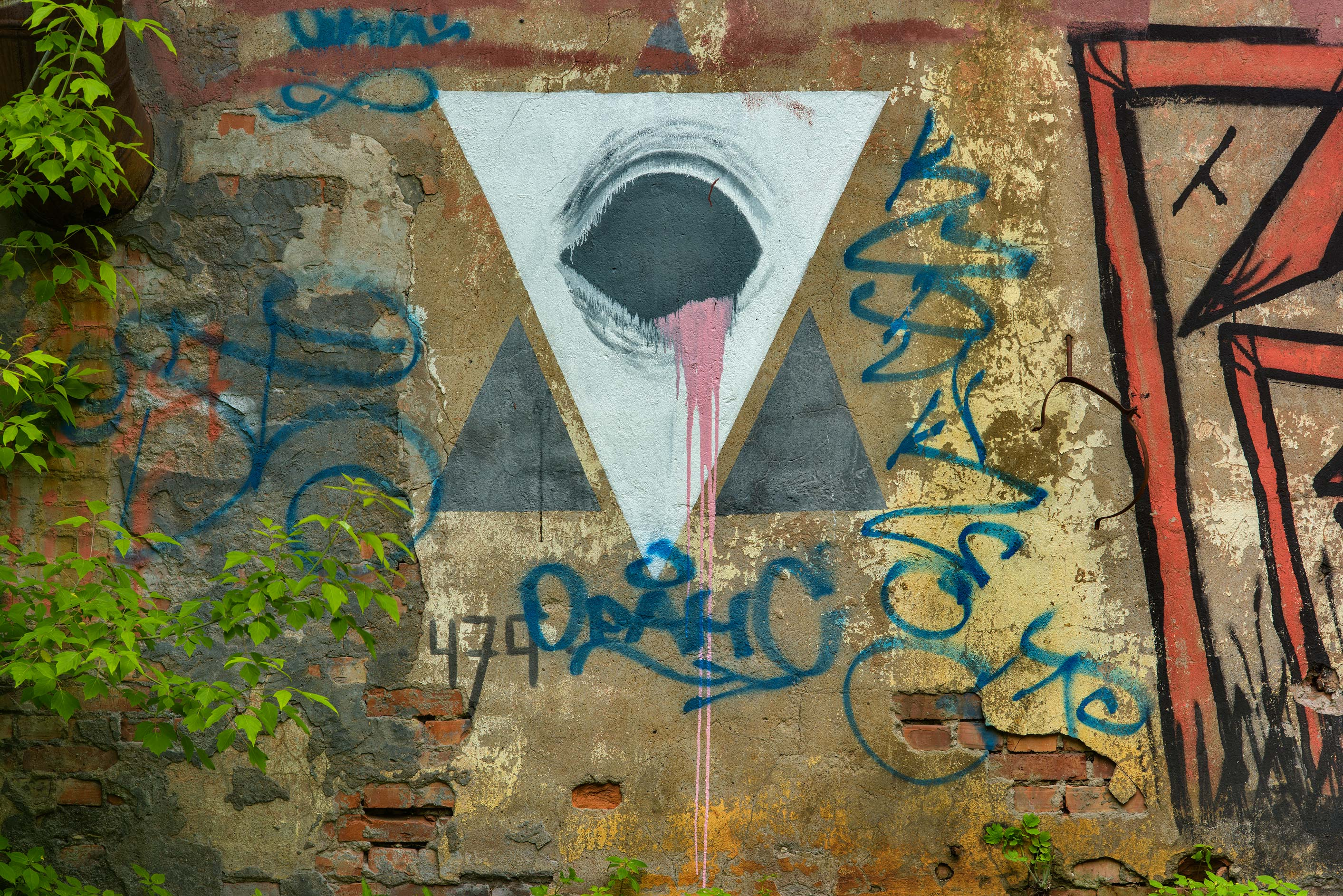 White triangle on graffiti on a house at 26K2...Island. St.Petersburg, Russia