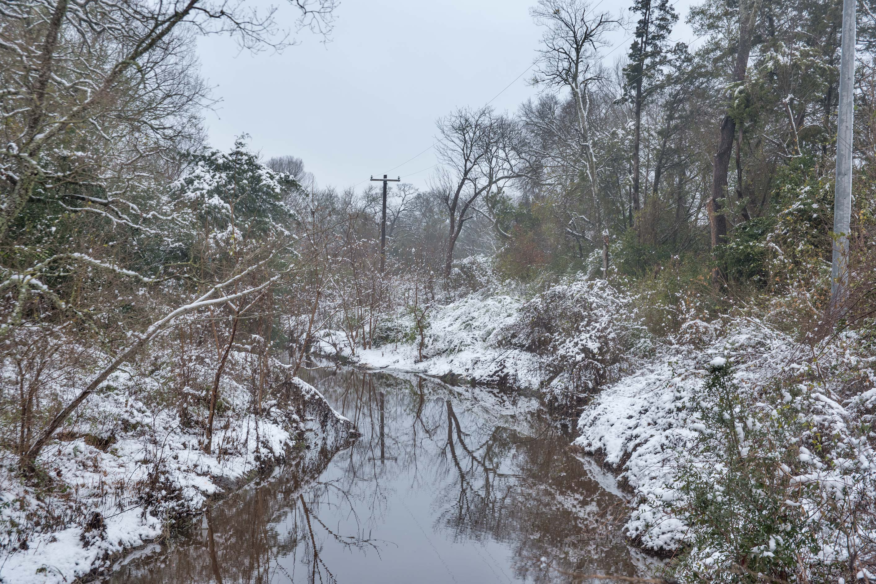 The creek in snow in Bee Creek Park. College Station, Texas